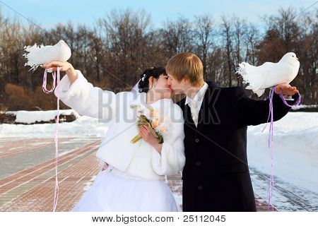 beautiful bride and groom hold white doves and kiss at winter outdoors
