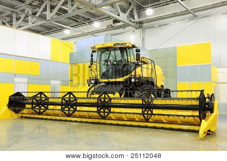Big yellow harvester are in room at exhibition, special agricultural machine
