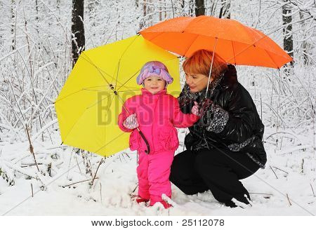Grandmother and granddaughter with yellow and orange umbrella stand in woods in snow at winter