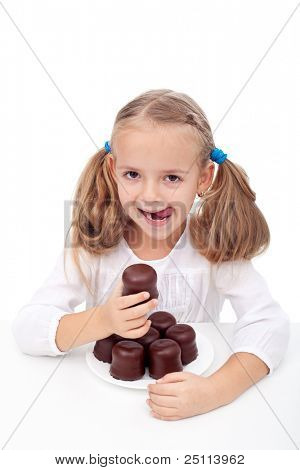 Little girl with a sweet tooth eating large chocolate coated cookies