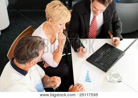 Mature couple with young financial consultant - they are planning their retirement