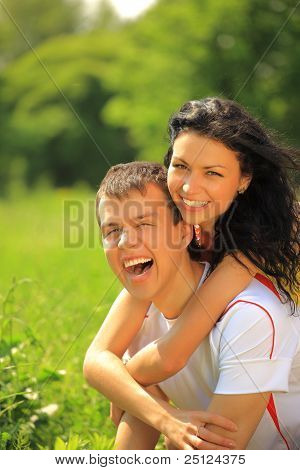 Portrait of happy young couple enjoying backriding outdoors