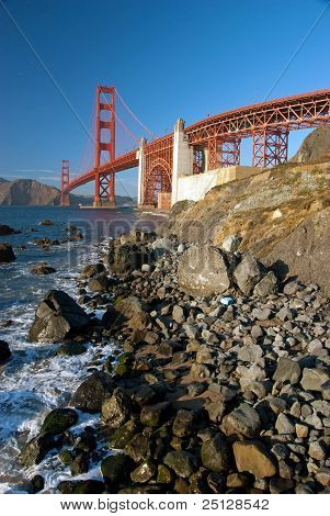 The Golden Gate Bridge In San Francisco During The Sunset With Rocks