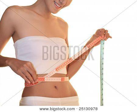 Ein Weibchen messen ihre Taille mit einem glücklichen Lächeln