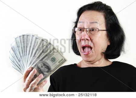 Asian lady holding a bunch of $100 bills with surprised facial expression