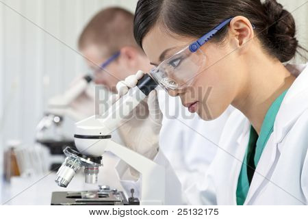 A Chinese Asian female medical or scientific researcher or doctor using a microscope in a laboratory with her colleague out of focus behind her.