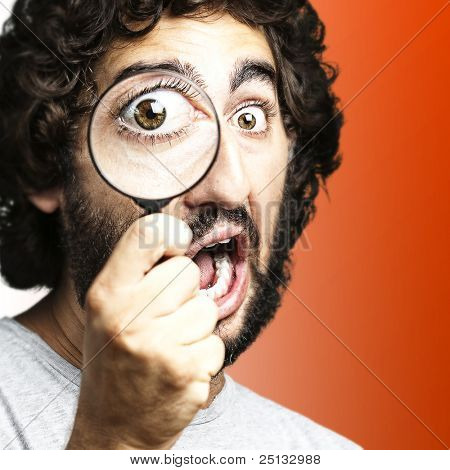 portrait of young man looking through a magnifying glass over red background