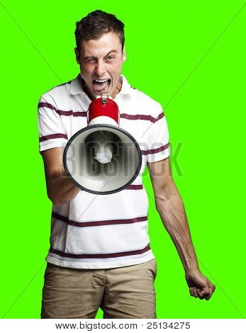 portrait of young man shouting with megaphone against a removable chroma key background