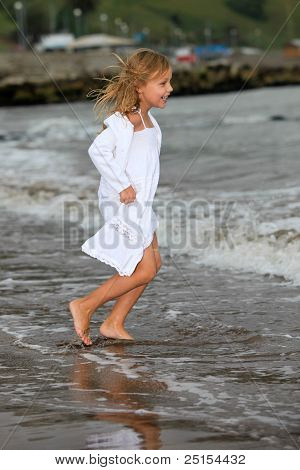 child running into the ocean