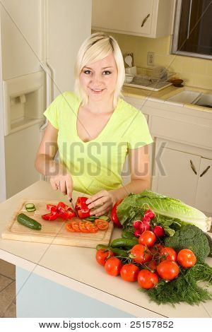 Young Blond Woman Slicing Vegetables On Kitchen
