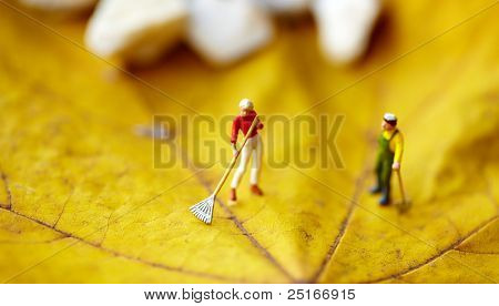 Miniature figurine  using a rake to clean up of the fallen leaves