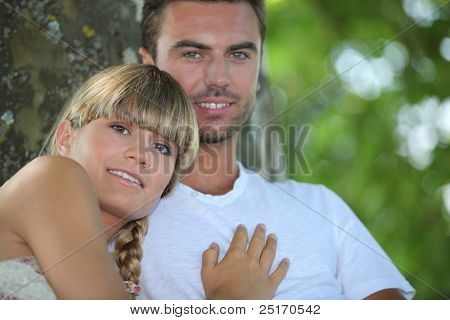 Couple sat by tree in park