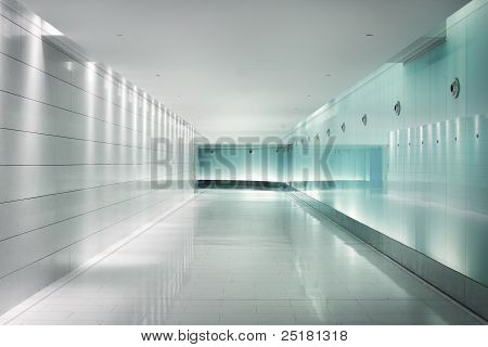 Back-lighted glass walls in an underground metro corridor