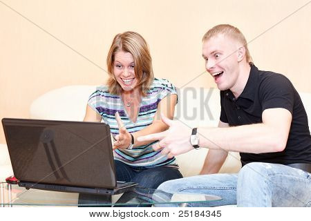Two persons playing in games on laptop