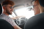 Smiling Couple Enjoying On A Long Drive In A Car. Friends Driving On Road Trip On Summer Day. Caucas poster