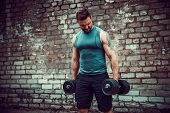 Athletic Man Working Out With A Dumbbell In Front Of Brick Wall. Strength And Motivation. Outdoor Wo poster