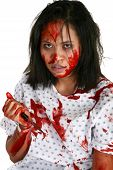 stock photo of domestic violence  - Young Indonesian woman covered in blood in hospital gown with knife - JPG