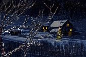 stock photo of snowy hill  - Snowy winter scene of a cabin in distance at night - JPG