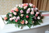 stock photo of sympathy  - White casket covered with floral arrangements at a funeral service