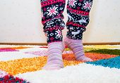 Womens Legs In Pajamas And Socks On The Bright Carpet. poster