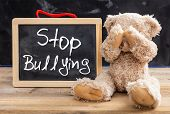 Teddy Bear Covering Eyes And Stop Bullying Text On A Blackboard poster