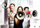 portrait of a angry  group of employees shouting using megaphones against a city background