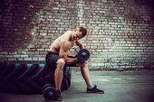 Athletic Man Working Out With A Dumbbell In Front Of Brick Wall While Sit On Big Tire. Strength And  poster