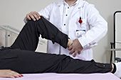 stock photo of physical therapist  - Leg massage physical therapy in hospital ward by male doctor - JPG