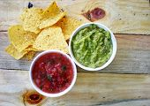 Tomato Salsa And Guacamole With Corn Tortilla Chips On A Wooden Boards poster