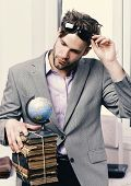 Academic Style And Modern Teaching Concept. Businessman With Pile Of Books And Globe Model On Window poster