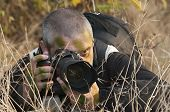 stock photo of camouflage  - Photojournalist working in the jungle camouflaged among the vegetation - JPG