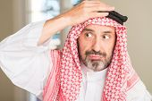 Middle age arabian man at home stressed with hand on head, shocked with shame and surprise face, ang poster