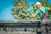 Roof And Gutters Power Cleaning Using Pressure Washer. Caucasian Worker. poster