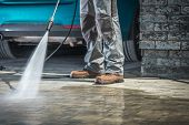 Cobble Stone Driveway Cleaning Using Pressure Washer With Concrete Cleaning Detergent. Closeup Photo poster
