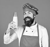 Cook With Happy Face In Burgundy Hat And Apron Presents Milk.. Nutritious Lactose Concept. Man With  poster
