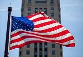 Close Up Of Waving Flag Of The United States In Downtown Chicago With High Building In The Backgroun poster