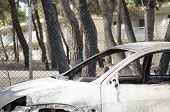 Fires In Greece Burnt Car On Road. Burnt Tire And Molten Metal poster