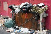 picture of dumpster  - overfilled trash dumpster in ghetto neigborhood against red wall - JPG