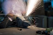 Selective Focus At Steel Rod And Motion Blurred. Man Use Electric Steel Cutter And Clamp Metal In Fa poster
