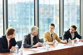 Modern confident business executives in formal suits sitting at conference table and arguing at meet poster