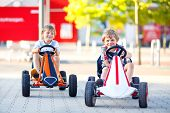 Two Active Little Kid Boys Driving Pedal Race Car In Summer Garden, Outdoors. Children, Best Friends poster