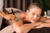 Relaxed mature woman enjoying a mud skin treatment at spa. Portrait of beautiful senior woman having poster