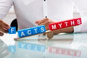 Businessman Showing Unbalance Between Facts And Myths poster