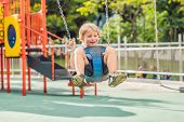 Funny Kid Boy Having Fun With Chain Swing On Outdoor Playground. Child Swinging On Warm Day. Active  poster