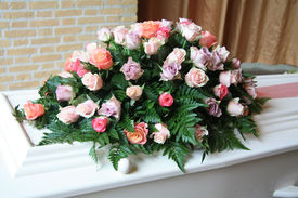 stock photo of funeral  - White casket covered with floral arrangements at a funeral service