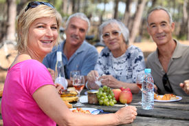 stock photo of mature adult  - Mature friends eating alfresco - JPG