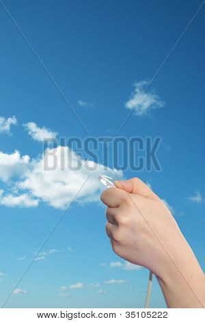 Concept or conceptual human or man hand holding a internet data cable in clouds over the blue sky, as a metaphor for plug,connection,technology,share,network,mobility,connect ivity or communication