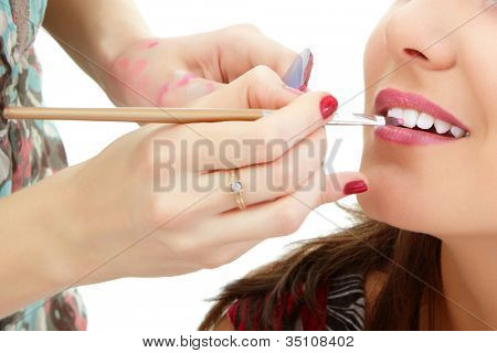 esthetician apply lipstick on female lips closeup, isolated on white background