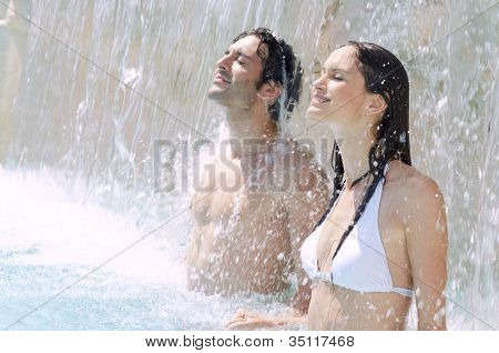 Joven pareja disfruta juntos la frescura de la cascada en una piscina