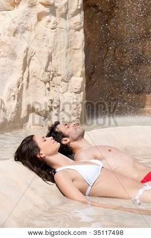Beautiful young couple relax together at the edge of a swimmingpool at spa centre